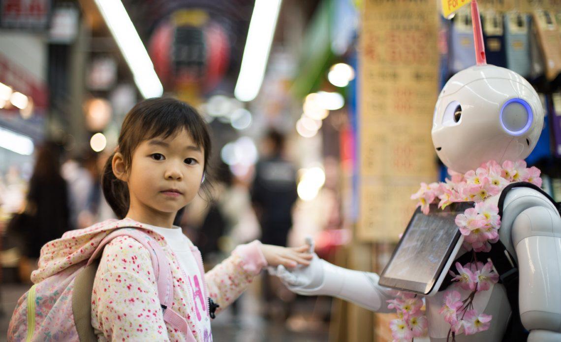 Child holding hand of robot